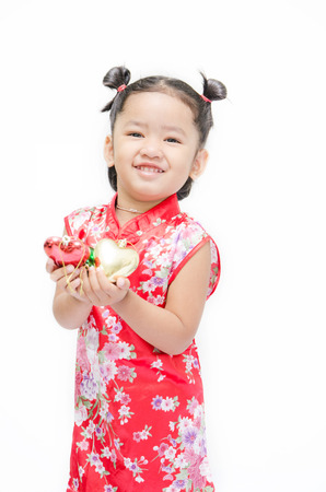 Cute asian girl in red chinese dress with heart in hand isolated on the white background