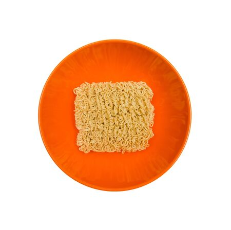Uncooked dry instant Noodle in orange bowl on the white background Stock Photo
