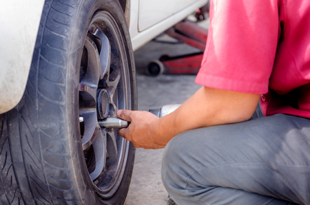 impact wrench: Close up shot of the hands of mechanics using pneumatic wrench to loosen the nut wheel of car