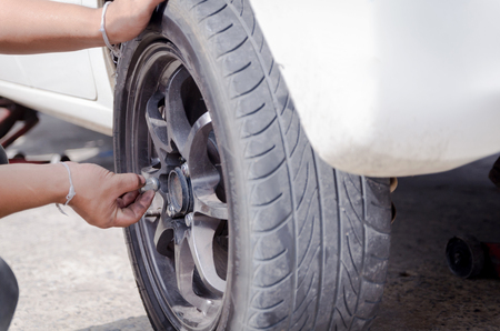 unscrewing: Hands of mechanic pick up the nut of car wheel and tighten Stock Photo