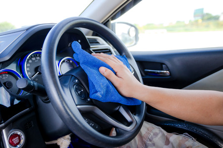 rag wheel: Close up hands of man using blue microfiber fabric to clean steering wheel