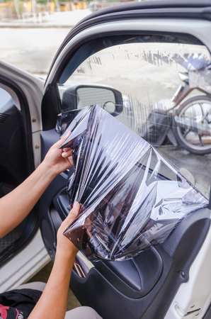 tinting: Hands of man removing old car window film Stock Photo