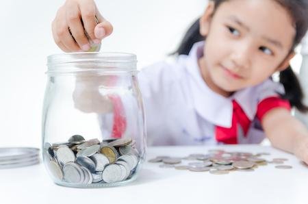 Niña asiática en uniforme de estudiante tailandés poniendo moneda a jarra de vidrio, se centran en la profundidad de campo de mano Foto de archivo - 69872535