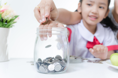 Asian little girl in Thai student uniform putting coin to glass jar with mother hand to saving money focus on hands shallow depth of field Foto de archivo
