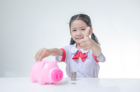 Asian little girl in Thai student uniform showing thumb up with piggy bank and stack of coins selective focus on face shallow depth of field