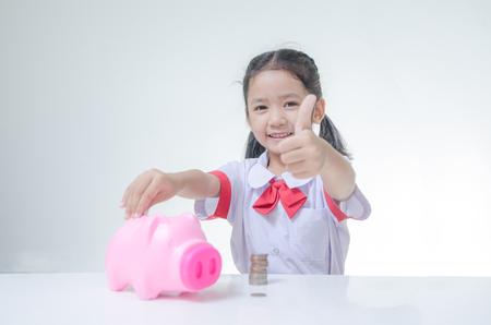 Aziatisch meisje in de Thaise student uniform met duim omhoog met spaarvarken en stapel munten selectieve focus op gezicht ondiepe scherptediepte