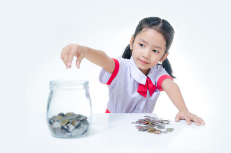 Asian little girl in Thai student uniform putting coin to glass jar, Focus on face shallow depth of field