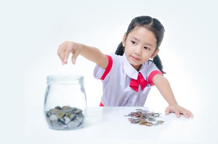 Asiatique petite fille en uniforme étudiant thaïlandais mettant la pièce dans un bocal en verre Banque d'images - 71318514