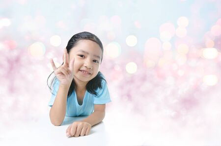 portait: Portait of smile Asian little girl showing  sign of love hand on bokeh background Stock Photo