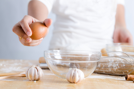 Close up shot hand of woman holding egg for braking shell with glass bowl to making bakery Stock Photo