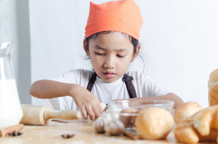 artisan bakery: Portrait of Asian little girl holding dough in hand and bakery on the wooden table over the white background, playing like a artisan breads