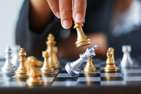 Close up Schuss Hand der Business-Frau bewegt sich golden Schach zu töten und zu töten Silber König Schach auf weiß und schwarz Schachbrett für Business Herausforderung Wettbewerb Gewinner und Verlierer Konzept, selektiven Fokus auf König Schach geringe Schärfentiefe Standard-Bild