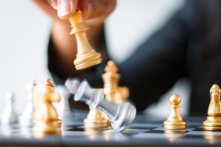 Sluit omhoog geschoten gouden schaak om zilveren schaak op schaakbord op witte en zwarte schaak te verslaan voor bedrijfsuitdagingsconcurriewinnaar en verliezerconcept, selectieve nadruk op koningsschaak ondiepe diepte van gebied, met motieonduidelijk beeldtechniek