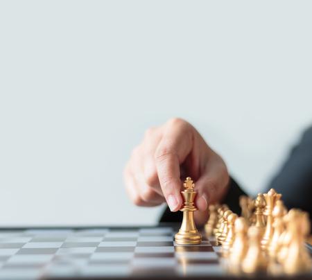 총을 닫습니다 실버 킹을 물리 치고 황금 체스를 이동하는 사업 여자의 손에 흰색과 검은 색 체스 보드 비즈니스 도전 경쟁을위한 승자와 패자 개념 복