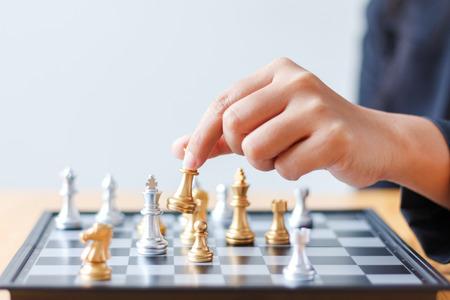Ciérrese encima de la mano del tiro de la mujer de negocios que mueve el ajedrez de oro para derrotar un ajedrez de plata del rey en el tablero de ajedrez blanco y negro para el concepto del ganador y de la competencia del desafío del negocio, foco selectivo en profundidad baja del ajedrez del rey del campo Foto de archivo - 85331642