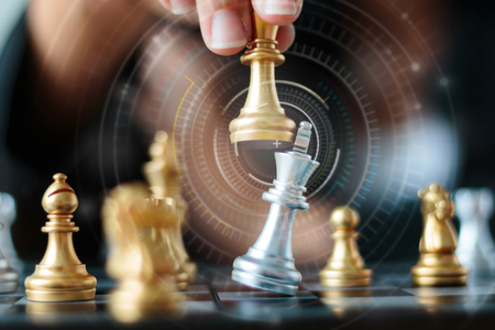Close up shot hand of business woman moving golden chess to defeat and kill silver king chess on white and black chess board for business challenge competition winner and loser concept, selective focus on king chess shallow depth of field, HUD lighting ef Foto de archivo