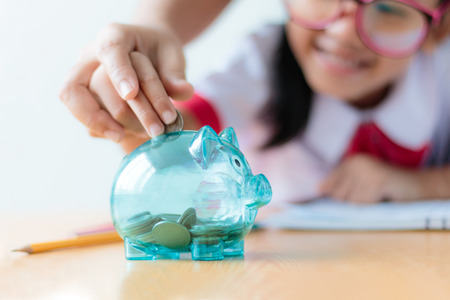 Close up shot Asian little girl in Thai student kindergarten uniform with mother hand putting money coin into clear piggy bank saving money for education concept shallow depth of field select focus on pig
