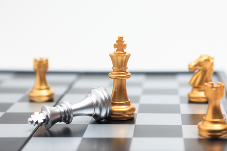 Chess board game gold player killed silver king for business competition metaphor winner and loser concept shallow depth of field Stock Photo