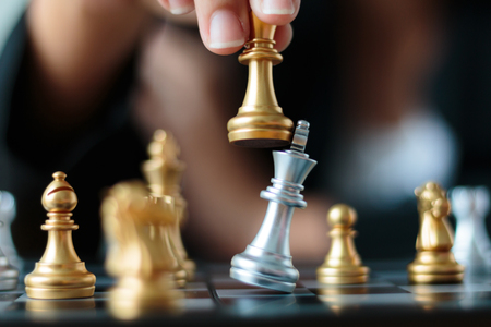 Close up shot hand of business woman moving golden chess to defeat and kill silver king chess on white and black chess board for business challenge competition winner and loser concept, selective focus on king chess shallow depth of field Stok Fotoğraf - 87159943