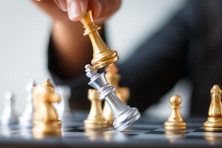 Sluit omhoog geschotene hand van bedrijfsvrouw bewegend gouden schaak om zilveren koningsschaak op witte en zwarte schaakraad te verslaan en te doden voor de winnaar en de verliezerconcept van de bedrijfsuitdagingsconcurrentie, selectieve nadruk op koningsschaak ondiepe diepte van gebied Stockfoto