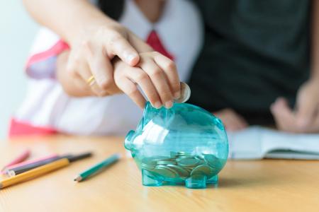 明確な貯金箱ブタ教育コンセプト選択フォーカスのフィールドの浅い深さのためのお金を節約お金のコインを入れて母の手でクローズ アップ ショッ