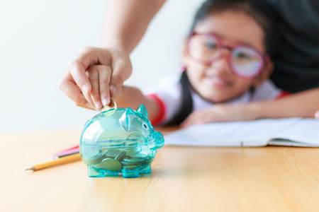 Sluit omhoog ontsproten Aziatisch meisje in Thaise studentende kleuterschool eenvormig met moederhand die geldmuntstuk zetten in duidelijk spaarvarken die geld voor onderwijsconcept besparen ondiepe diepte van gebiedselectie nadruk op varken