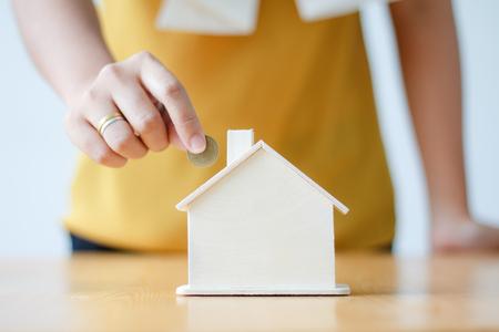 De Aziatische vrouw die geldmuntstuk binnenbrengen om spaarvarken van de huisspaarvarken metafoor te bewaren voor koopt de huis ondiepe diepte van gebieds geselecteerde nadruk op huis Stockfoto