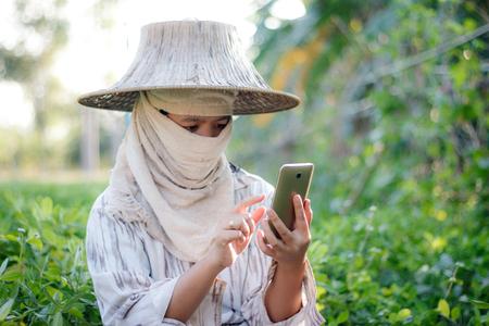 Sluit omhoog geschotene landbouwer gebruikend mobiele smartphone in het aardlandbouwbedrijf met omgevingslicht Stockfoto