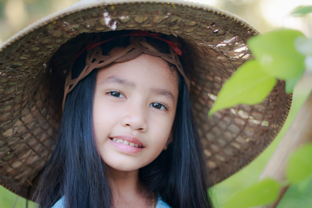 Portrait close up shot Asian little girl wearing farmer hat in green nature farm with happiness