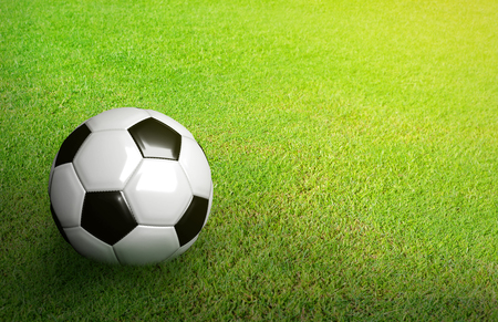 3D Rendered black and white soccer ball on green soccer football field background with copy space and grain processed