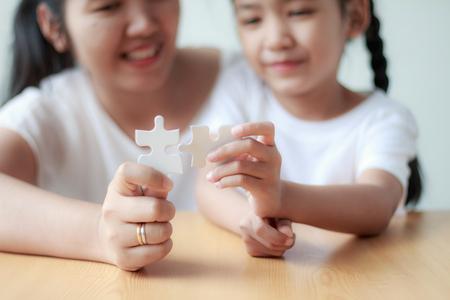 Aziatische meisje het spelen puzzel met haar moeder voor de ondiepe diepte van het familieconcept van gebied uitgezochte nadruk op handen