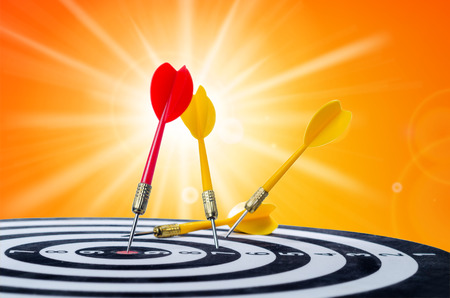 Close up shot red dart arrow on center of dartboard and yellow arrow not hit the target,  on yellow backgkround metaphor to target success, winner and loser concept