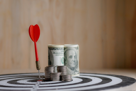 Red dart arrow hit the center target of dartboard and money coin metaphor marketing or saving money concept, on wood background