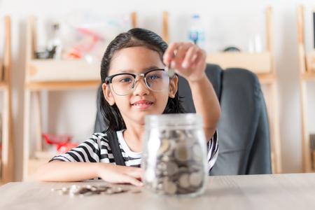 Asiatisches kleines Mädchen beim Einlegen der Münze in das Glas zum Sparen von Geld Konzept flache Schärfentiefe wählen Fokus im Gesicht