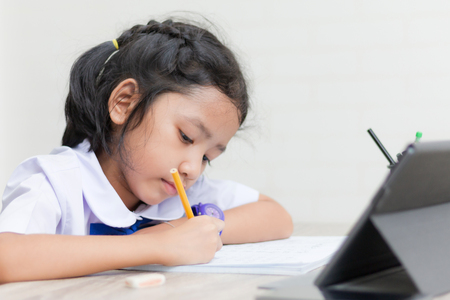 Asian little girl in student uniform doing homework on wooden table with tablet select focus shallow depth of field