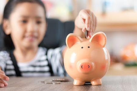 Asiatisches kleines Mädchen beim Einlegen der Münze in die flache Schärfentiefe des Sparschweins wählen den Fokus auf das Schwein