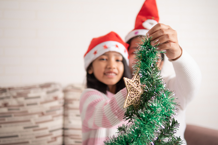 Asian little girl with mother decorating christmas tree for party with happiness, Select focus shallow depth of fie
