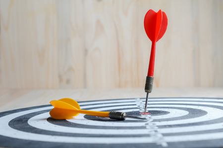 Winner Red dart arrow hit the center target of dartboard and yellow arrow loser metaphor marketing competition concept, on wood background