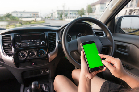 Hand of woman using smartphone with blank green screen monitor in SUV car