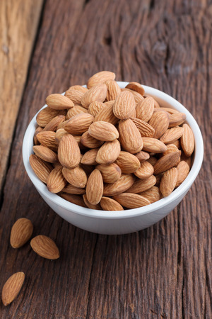 Almond nut in a ceramic bowl against wooden table, select focus shallow depth of field Stock Photo