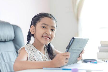 Niña asiática que usa la tableta y sonríe con felicidad para el concepto de educación seleccione enfoque profundidad de campo