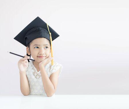 Ritratto piccola ragazza asiatica indossa cappello laureato tenendo la matita seduto pensando qualcosa e sorridere con felicità selezionare messa a fuoco profondità di campo con spazio copia per il concetto di educazione