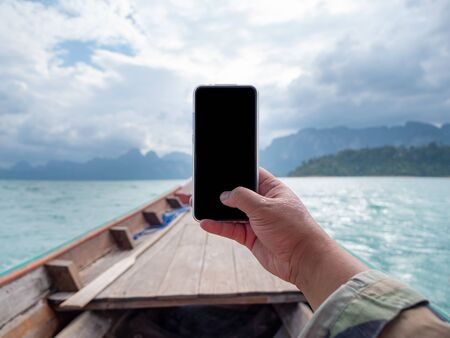 Hand of man using mobile smart phone against scenic landscape of boat view in the big river and reservoir dam with mountain and nature forest