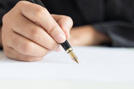Nahaufnahme der geschossenen Hand der Geschäftsfrau, die den Stift verwendet, um auf dem Weißbuch zu schreiben, wählen Sie den Fokus geringe Schärfentiefe Standard-Bild