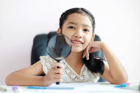 Little Asian girl using magnifier doing homework and smile with happiness for education concept select focus shallow depth of field