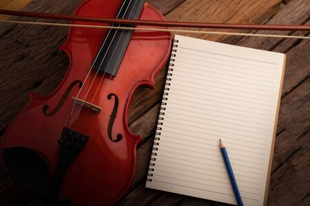 Close-up shot violin orchestra instrumental and notebook over wooden background select focus shallow depth of field