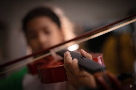 Close-up shot little girl playing violin orchestra instrumental with vintage tone and lighting effect dark and grain processed select focus shallow depth of field Stock Photo