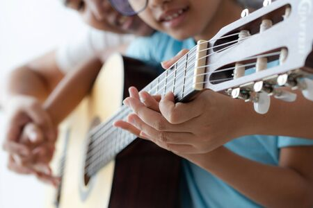Mother teaching the daughter learning how to play acoustic classic guitar for jazz and easy listening song select focus shallow depth of field