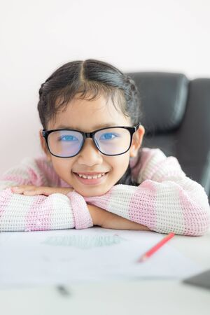 Little Asian girl doing homework and smile with happiness for education concept select focus shallow depth of field Archivio Fotografico