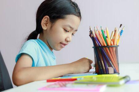 Klein Aziatisch meisje dat huiswerk doet, kleurpotlood gebruikt om op papier te tekenen, focus ondiepe scherptediepte selecteert